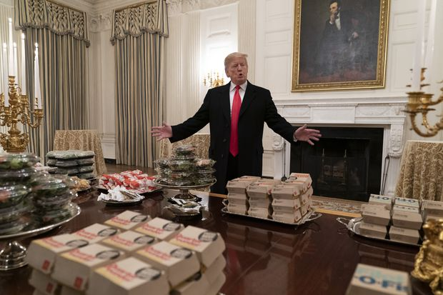 Trump presenting a buffet of fast food to be served to the Clemson Tigers football team. Chris Kleponis/Pool/Getty Images