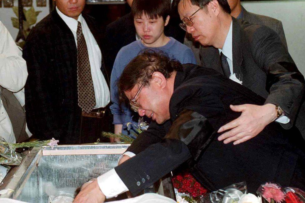 BORIS SUBASIC/EPA Image caption The father of Zhu Ying weeps over her coffin in Belgrade