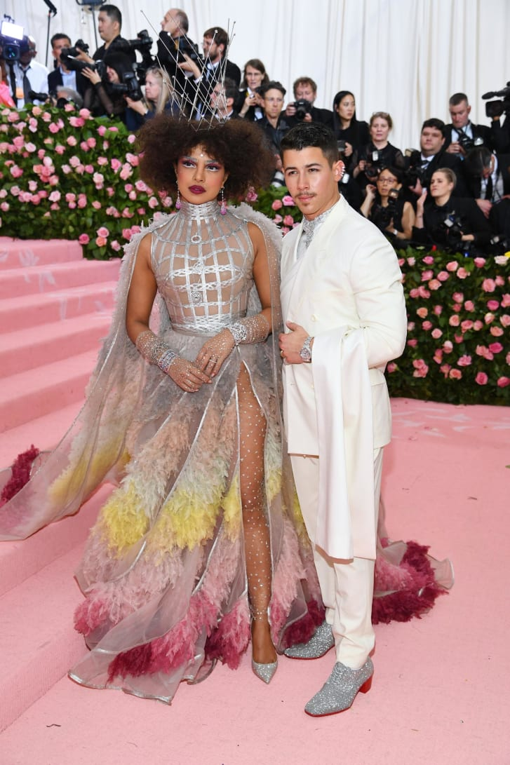 "Last month, Nick Jonas told Entertainment Tonight that his wife Priyanka Chopra would ""set the tone"" for the pair's Met Gala outfits. The Bollywood star did just that, wowing onlookers in a stunning feather dress by Dior Haute Couture. Jonas complemented the look with silver shoes and a silver shirt peeking out from his Dior Men white suit. The Met Gala has a special place in the pair's romantic history: They made their first public appearance together at the 2017 event, which they attended as guests of Ralph Lauren."