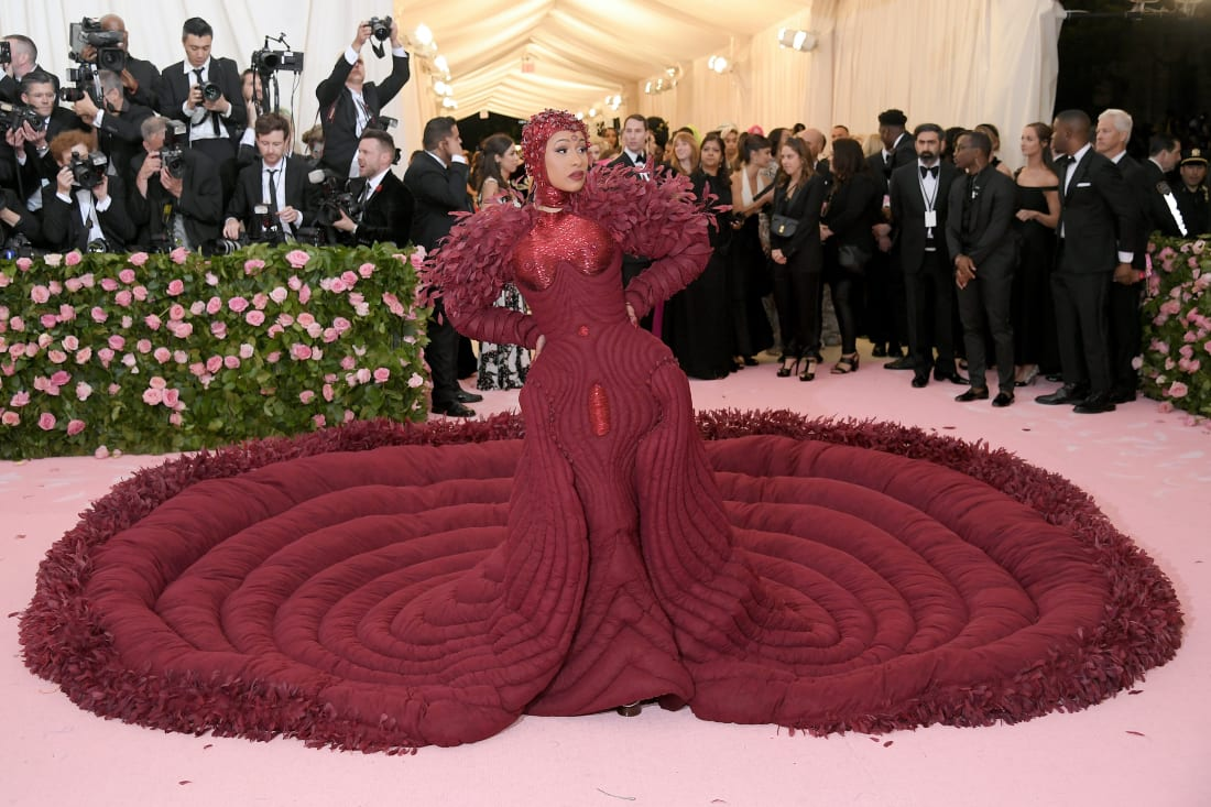 Rapper Cardi B showed up to the Met Gala in a dramatic burgundy gown that extended into a full quilted circular train. The dress, which is trimmed in feathers, was designed by Thom Browne. She also has a matching headpiece on to complete the head-to-toe scarlet look. The dress was decorated with 30,000 feathers, and took 35 people more than 2,000 hours to make.Neilson Barnard/Getty Images