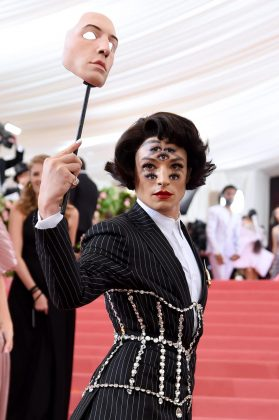 Ezra Miller arrived on the red carpet wearing a Burberry-designed outfit, which included a white dress shirt and a mask. But all eyes were on Miller, as he removed the mask to reveal a seven-eyed look paired with a black pinstriped suit and an overlaid crystal-studded corset.